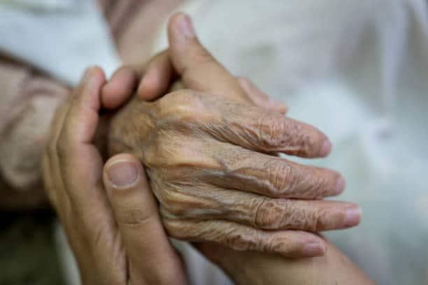 Aide-soignante qui tient les mains à une personne âgée en situation de perte d'autonomie