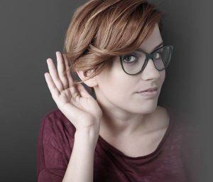 Femme qui essaie d'entendre la main derrière l'oreille