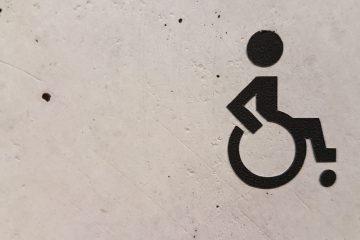 Symbole handicapé sur un mur blanc